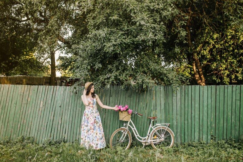 Śliczna dziewczyna w kwiatu kapeluszu i sukni jest trwanie pobliskim zieleni ogrodzeniem, drzewami i Jej biały rocznika bicykl z  zdjęcia royalty free