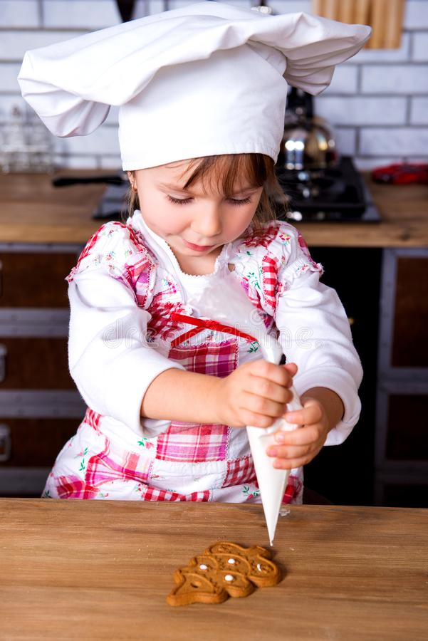 Śliczna dziewczyna w szefa kuchni kulinarnym kapeluszu dekoruje konfekcyjną piec piernikową choinki figurkę z słodkim lodowacenie obraz stock
