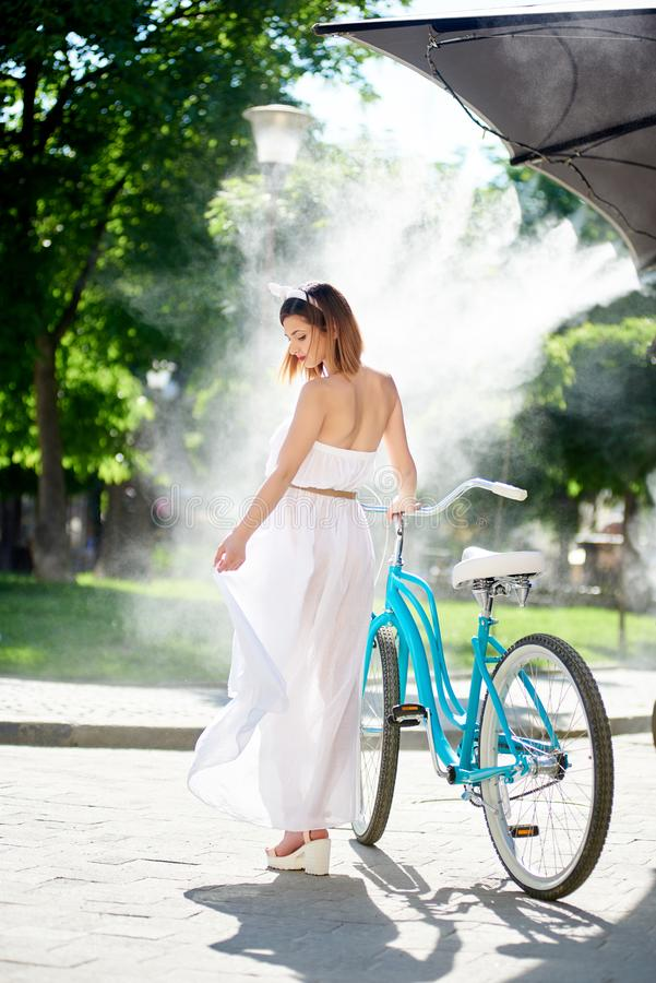 Śliczna dziewczyna z bicyklem pod mglistym systemem lato kawiarnia fotografia stock
