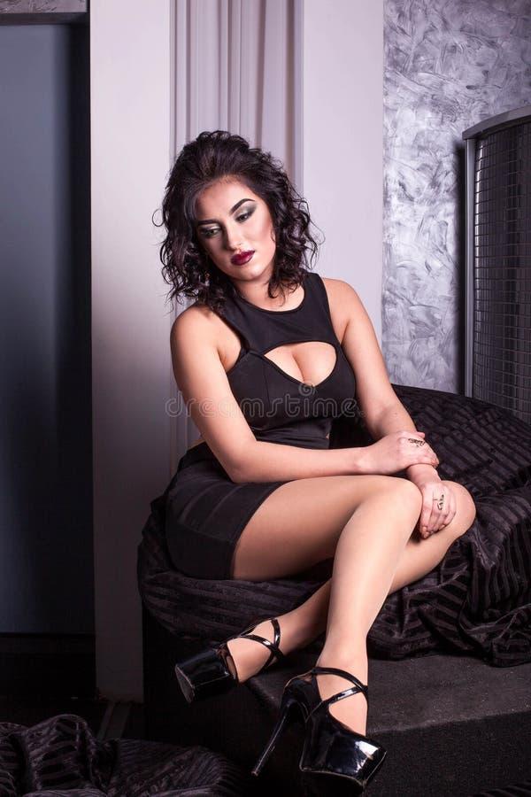 Śliczna dziewczyna z kędzierzawym włosy i baeutiful smokingowy obsiadanie na miękkim krześle w barze obrazy royalty free