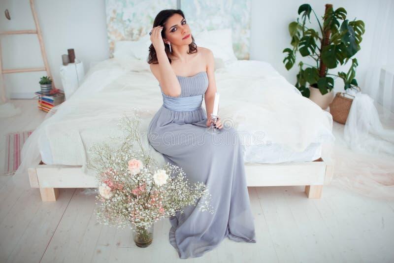 Śliczna dziewczyna z makeup w błękitnym wieczór sukni obsiadaniu na łóżku W rękach trzyma świeczkę fotografia stock