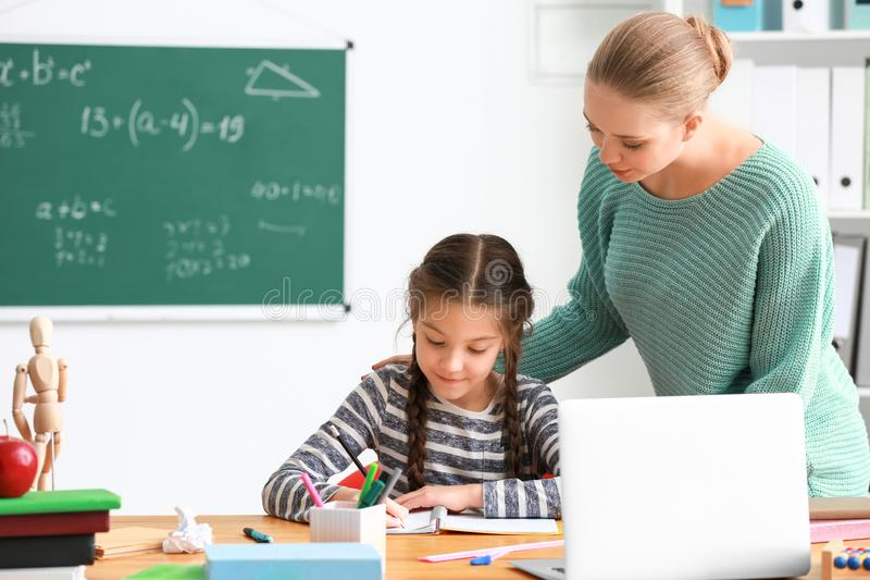 Śliczna dziewczyna z nauczycielem robi pracie domowej w sali lekcyjnej fotografia royalty free