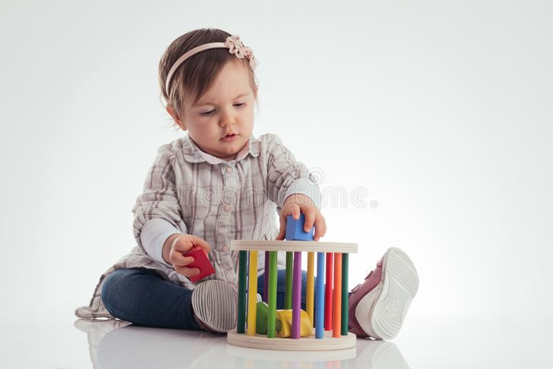 Śliczna dziewczynka bawić się drewnianych sześciany na białym tle fotografia stock
