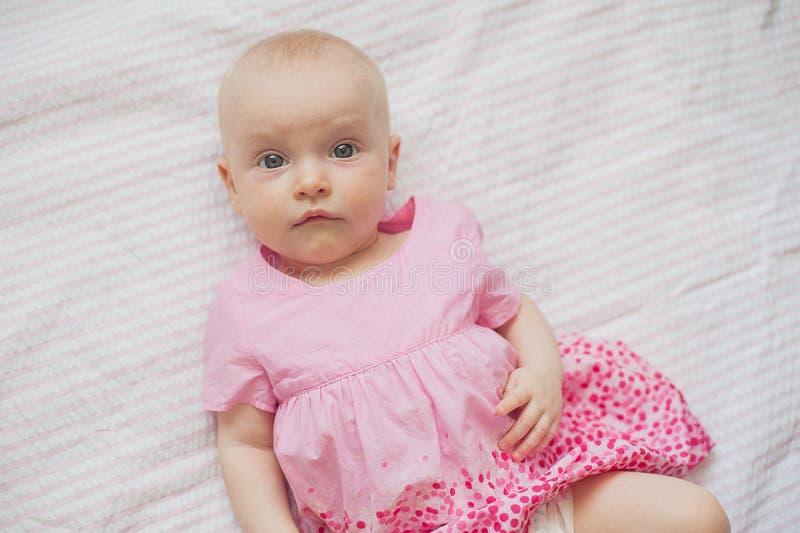 Śliczna dziewczynka w menchii sukni kłama na białym backgroun nowonarodzone dziecko zdjęcie stock