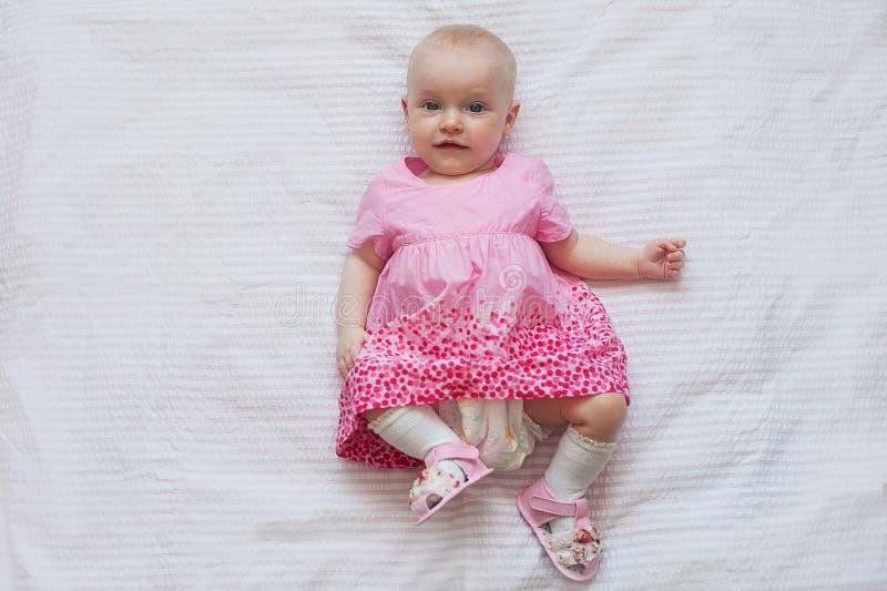 Śliczna dziewczynka w menchii sukni kłama na białym backgroun nowonarodzone dziecko obraz stock