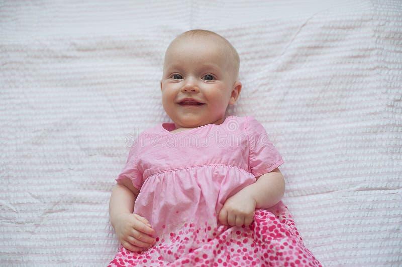 Śliczna dziewczynka w menchii sukni kłama na białym backgroun Zakończenie portret, uśmiechnięty dziecko zdjęcie royalty free
