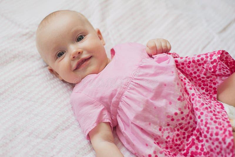 Śliczna dziewczynka w menchii sukni kłama na białym backgroun Zakończenie portret, uśmiechnięty dziecko zdjęcia stock