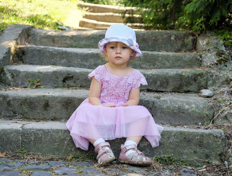 Śliczna dziewczynka z grafitowymi oczami siedzi zamyślenie na antycznych kamiennych krokach zakrywających z mech obrazy stock