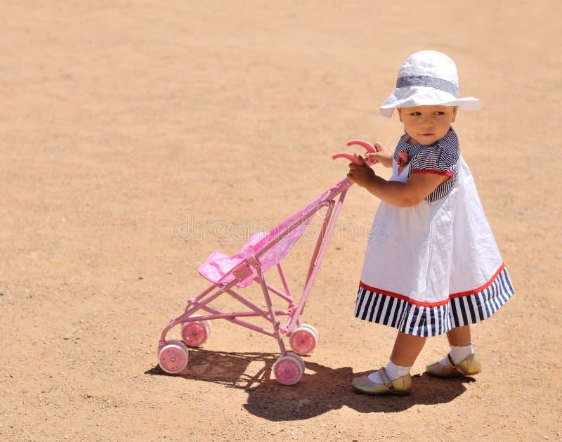 Śliczna dziewczynka z zabawkarskim spacerowiczem zdjęcia royalty free