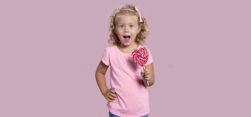 Śliczna dziewczynka z zielonymi oczami i lalypop odizolowywający nad różowym tłem fotografia royalty free