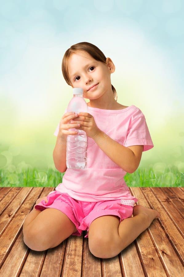 Śliczna dziewczyny mienia butelka woda fotografia royalty free