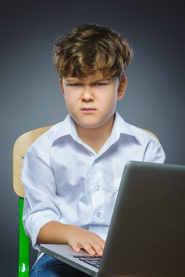 Śliczna gniewna lub zaakcentowana chłopiec używa laptop odizolowywającego popielatego tło zdjęcia stock