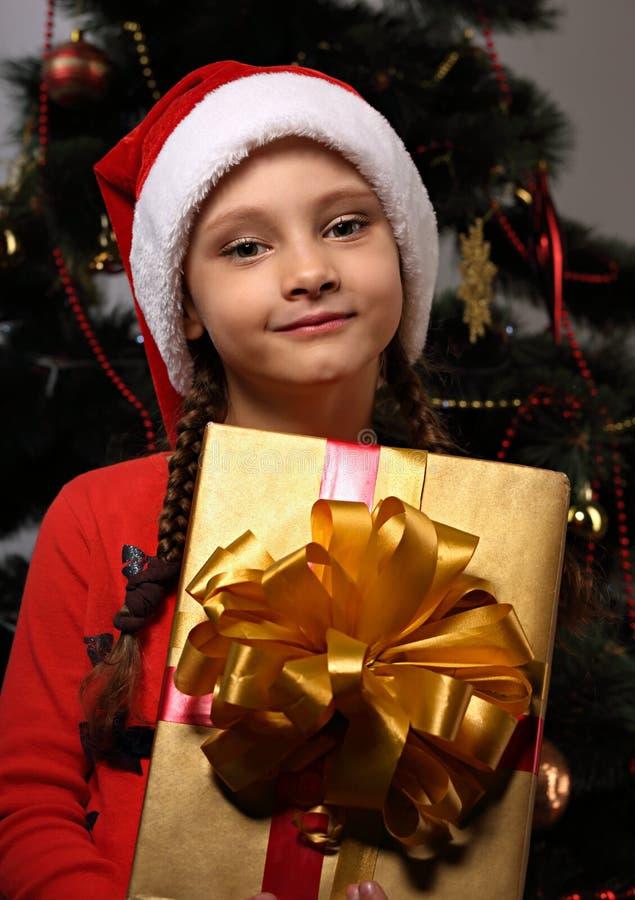 Śliczna grimacing dzieciak dziewczyna trzyma w Bożenarodzeniowym Santa Claus kapeluszu zdjęcia stock
