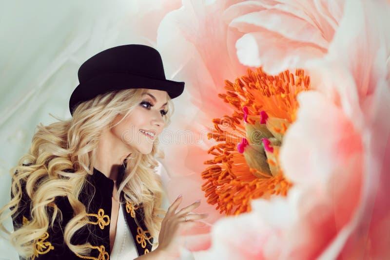 Śliczna i piękna blondynka z zadziwiającym ogromnym kwiatem Powabna młoda kobieta w curvy błękit spódnicie zdjęcia stock