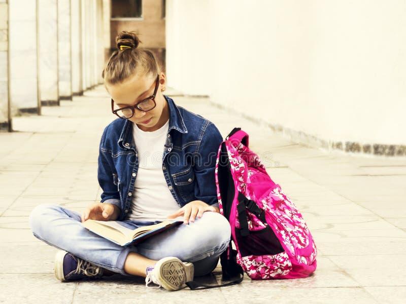 Śliczna jasnogłowa dziewczyny uczennica czyta książkę podczas gdy siedząca pobliska szkoła Edukacja zdjęcia stock