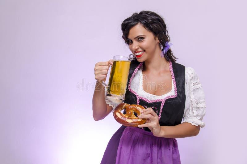 Śliczna kędzierzawego włosy dziewczyna w Oktoberfest smokingowy ono uśmiecha się obraz royalty free