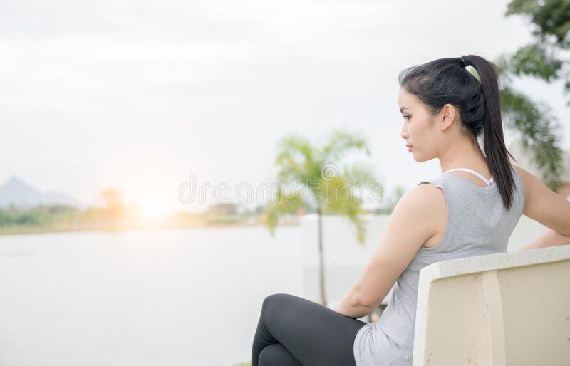 Śliczna kobieta siedzi na krześle blisko jeziora z wschodem słońca zdjęcie stock
