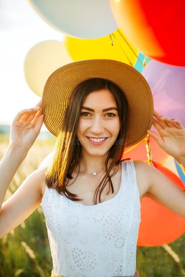 Śliczna kobieta trzyma wiązkę kolorowi balony fotografia royalty free