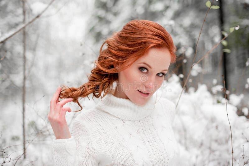 Śliczna kobieta w białym pulowerze w śnieżnym lesie zdjęcia royalty free