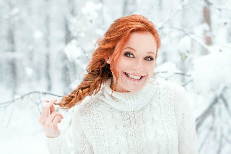 Śliczna kobieta w białym pulowerze w śnieżnym lesie obraz stock