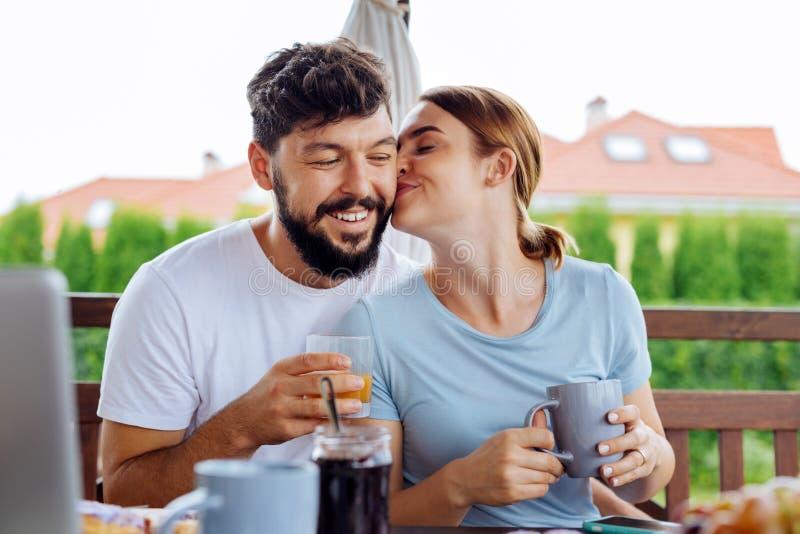 Śliczna kochająca kobieta całuje jej męża podczas gdy pijący kawę obrazy stock