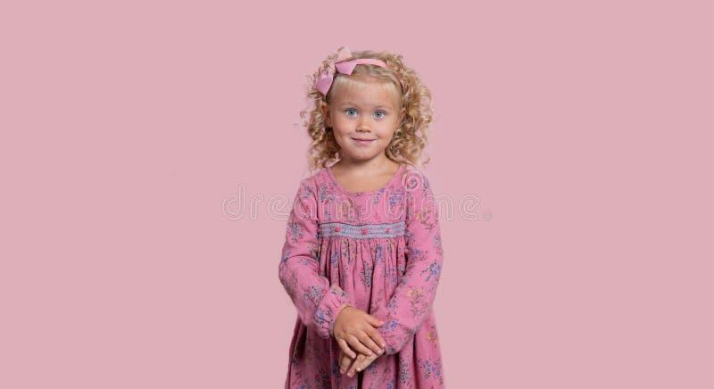 Śliczna 3-letni stara blond dziewczyna w różowym stroju z pięknymi zielonymi oczami Różowy tło zdjęcia stock