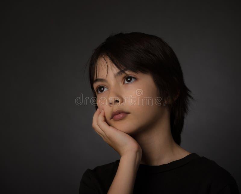 Śliczna młoda azjatykcia chłopiec przyglądająca z poważnym spojrzeniem na czarnym backg up obraz stock