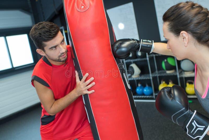 Śliczna młoda brunetka dostaje bokserskie lekcje od trenera zdjęcia stock