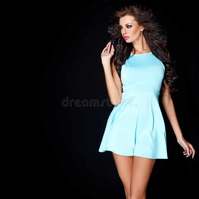 Śliczna młoda brunetka pozuje w błękit sukni zdjęcia stock