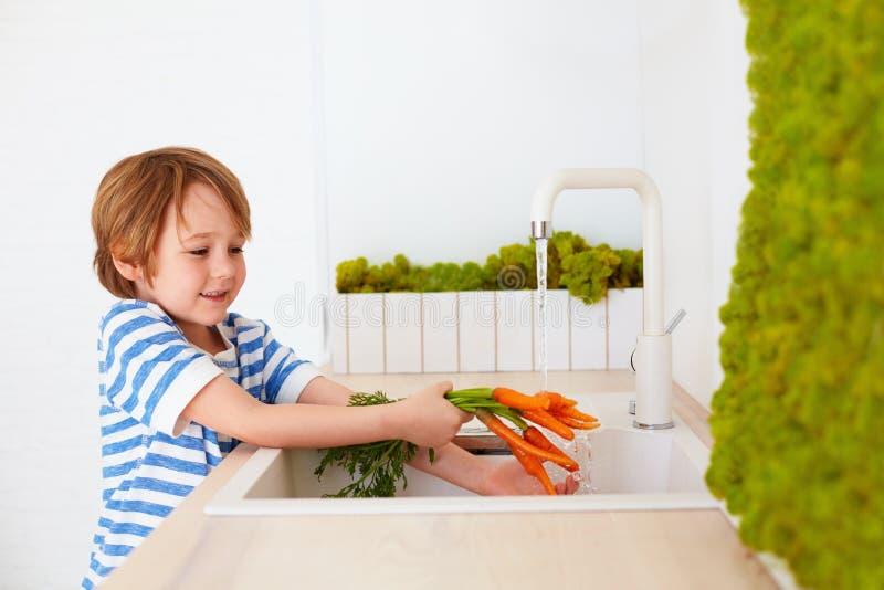 Śliczna młoda chłopiec myje marchewki pod wodą kranową w kuchni obrazy stock