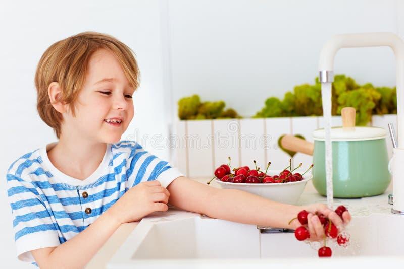 Śliczna młoda chłopiec myje naręcze słodkie wiśnie pod wodą kranową w kuchni obraz stock