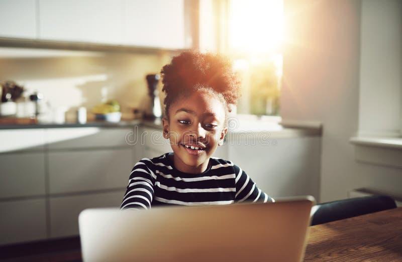Śliczna młoda czarna dziewczyna bawić się na laptopie zdjęcia royalty free