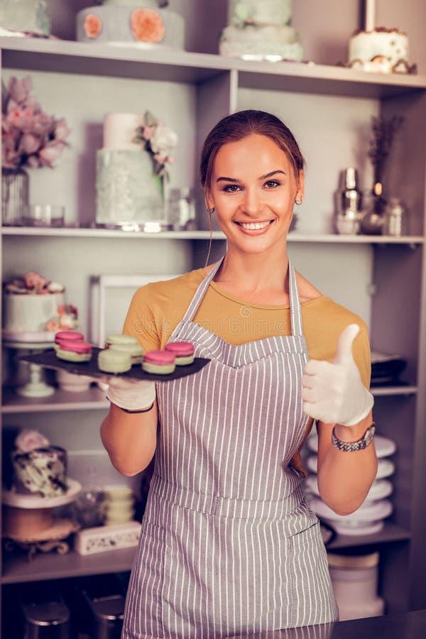 Śliczna młoda dziewczyna demonstruje talerza z macarons zdjęcie stock