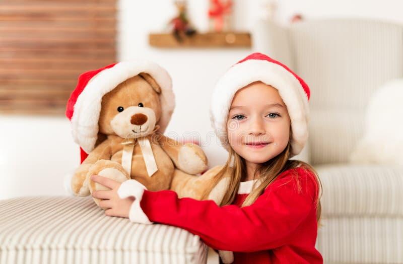 Śliczna młoda dziewczyna jest ubranym Santa kapelusz trzyma jej boże narodzenie teraźniejszość, miękka część zabawkarski miś Szcz zdjęcia stock