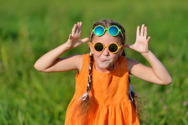 Śliczna młoda dziewczyna w słońc szkłach Hamming ma zabawę outdoors obraz royalty free