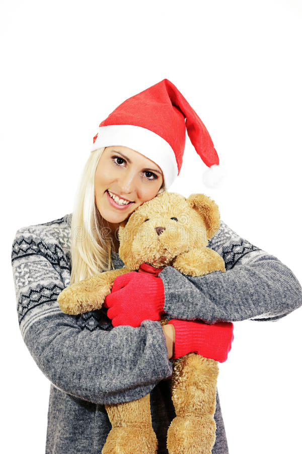Śliczna młoda dziewczyna z Święty Mikołaj kapeluszem, ściska misia fotografia royalty free