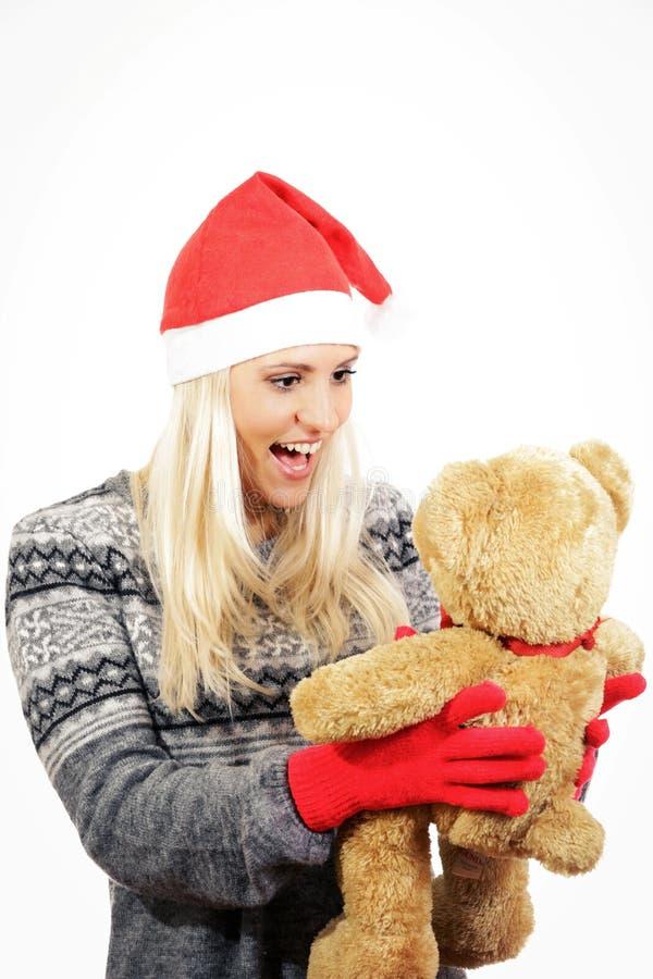 Śliczna młoda dziewczyna z Święty Mikołaj kapeluszem, ściska misia zdjęcie royalty free