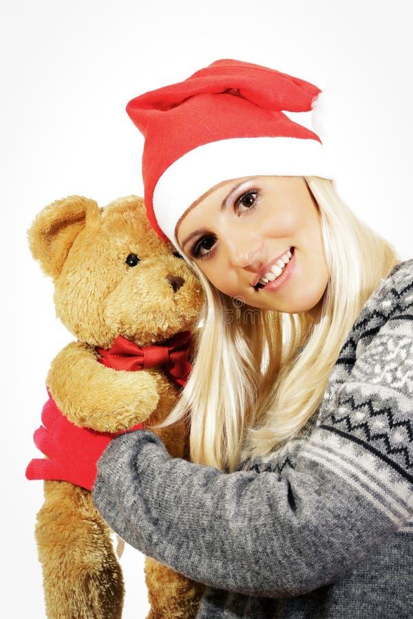 Śliczna młoda dziewczyna z Święty Mikołaj kapeluszem, ściska misia fotografia stock