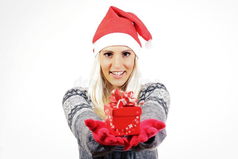 Śliczna młoda dziewczyna z Święty Mikołaj kapeluszem, trzyma teraźniejszość obraz stock