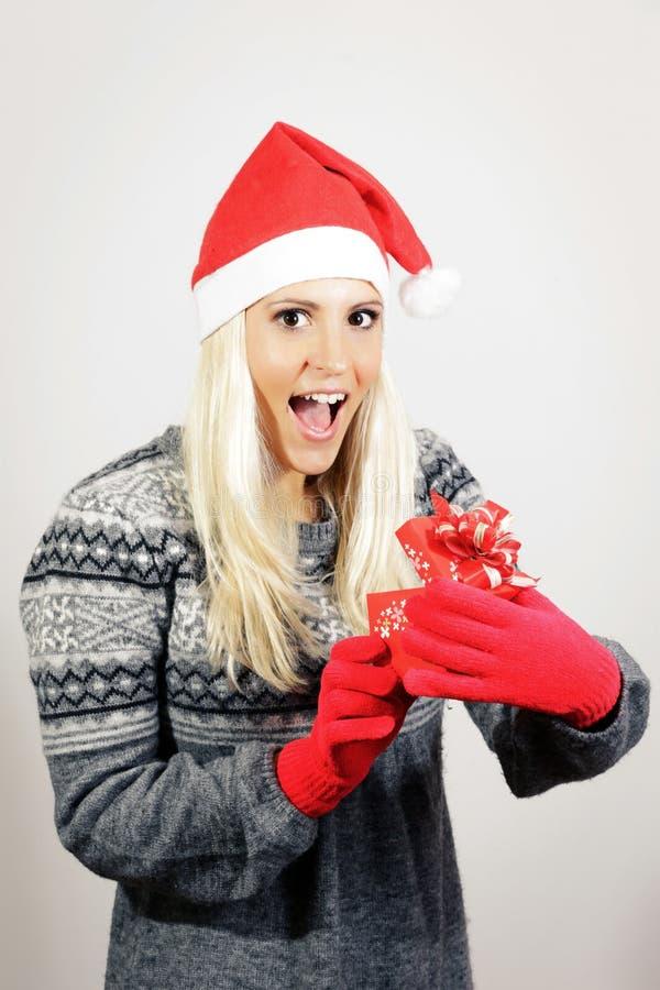 Śliczna młoda dziewczyna z Święty Mikołaj kapeluszem, trzyma teraźniejszość zdjęcia royalty free