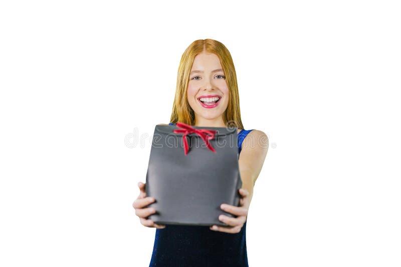 Śliczna młoda dziewczyna z długim czerwonym włosy trzyma czarnego wyłączności na wywiad pudełko z prezentem i ono uśmiecha się pr fotografia stock