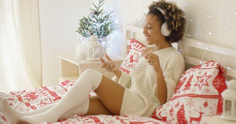 Śliczna młoda kobieta cieszy się jej muzykę przy Xmas obraz royalty free