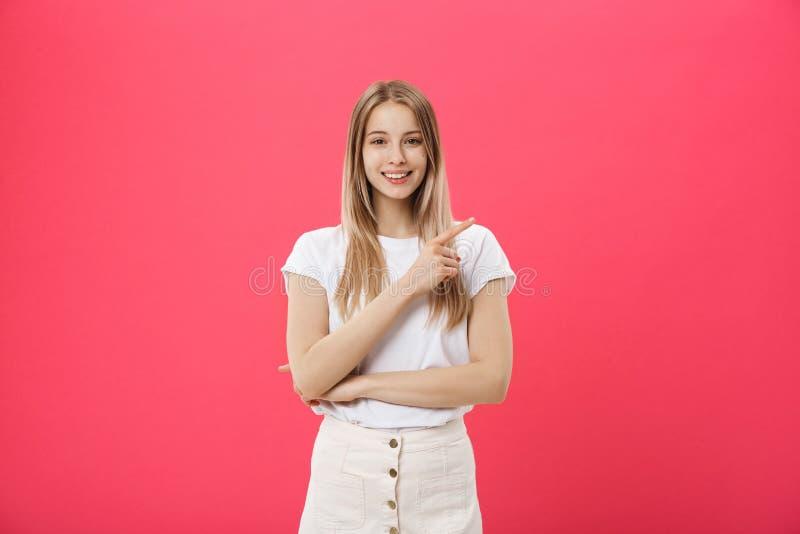 Śliczna młoda kobieta jest ubranym białą koszulkę wskazuje palcowego daleko od odizolowywającego nad różowym tłem obrazy royalty free