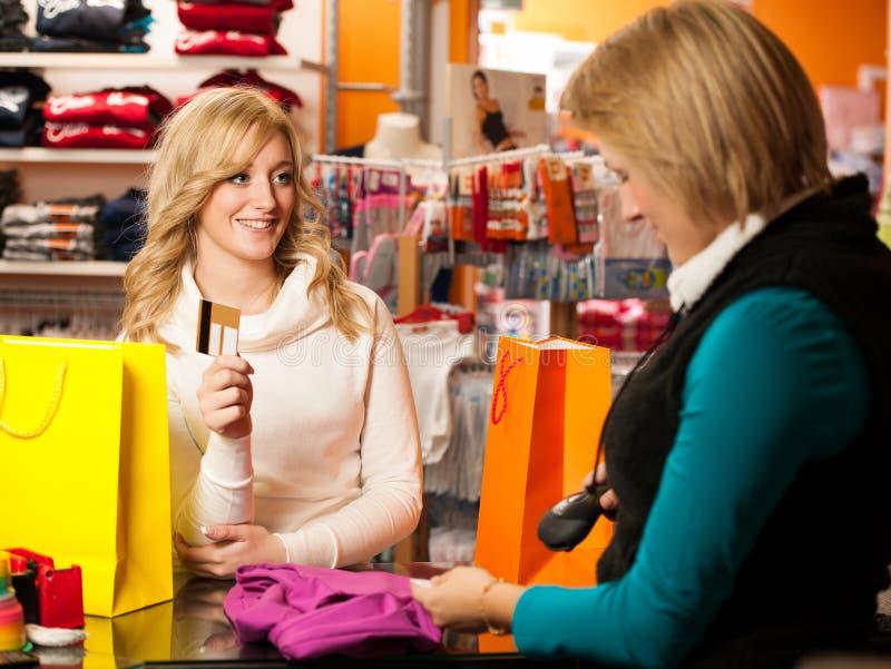 Śliczna młoda kobieta płaci po succesfull zakupu  zdjęcie stock