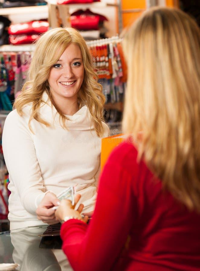 Śliczna młoda kobieta płaci po succesfull zakupu  zdjęcie royalty free