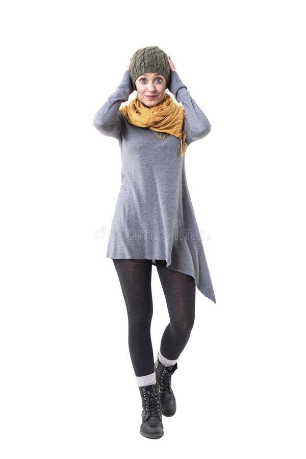Śliczna młoda kobieta patrzeje kamerę w autentycznego unikalnego stylu odzieżowego mienia zwełnionej nakrętce zdjęcie stock