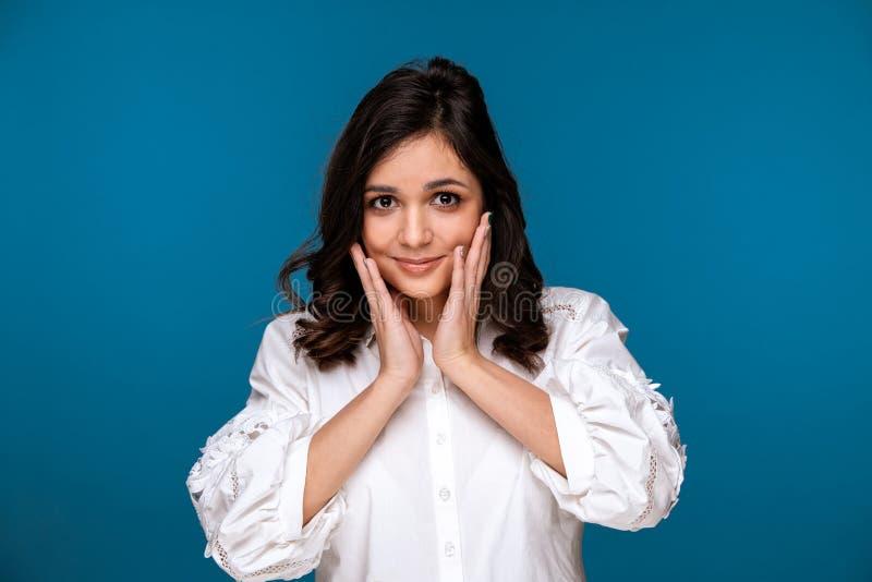 Śliczna młoda kobieta pozuje w studiu i trzyma ręki na jej twarzy obraz stock
