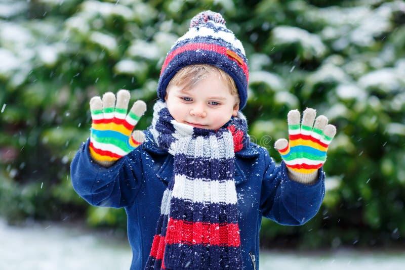 Śliczna mała śmieszna dzieciak chłopiec w kolorowych zimy mody ubraniach ma zabawę i bawić się z śniegiem podczas opadu śniegu, o fotografia stock