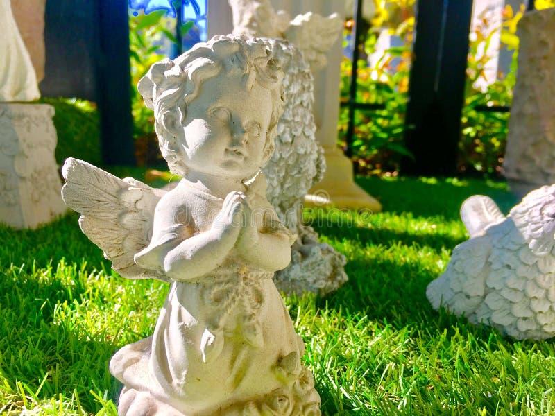 Śliczna mała anioł statua na trawie z światłem słonecznym zdjęcie royalty free