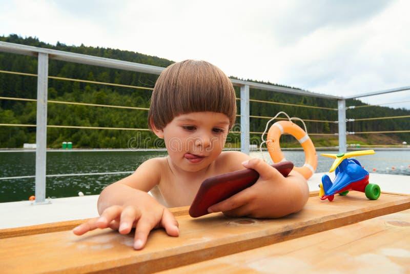 Śliczna mała berbeć chłopiec bawić się gry na jego mądrze telefonie zdjęcie royalty free
